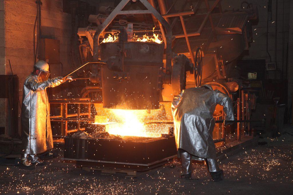 Giesserei, Arbeiter giessen Stahl in eine Sandform. Sand solcher Formen kann durch die Giessereiltsandverwertung nachhaltig entsorgt werden.